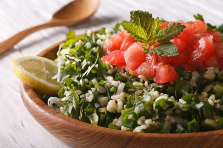 tabbouleh: Classic Tabbouleh salad macro in a wooden bowl Stock Photo