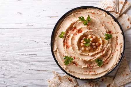 Hummus classico con prezzemolo sul pane piatto e pita