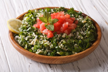 tabbouleh: Tabbouleh salad closeup in a wooden bowl on the table Stock Photo