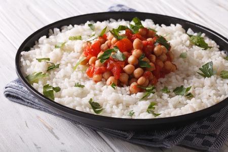 arroz: Los garbanzos en salsa de tomate con arroz en un plato de cerca