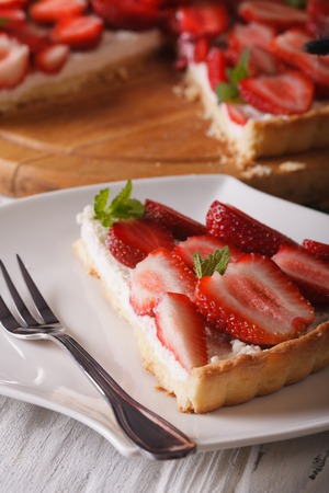 a piece of strawberry tart with cream cheese on a plate close-up. vertical photo