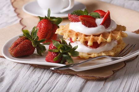 dessert topping: Delicious dessert: waffles with fresh strawberries and cream close-up on a plate. horizontal