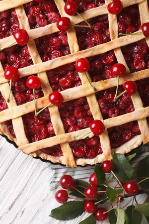cherry pie and ripe berries close-up on the table. vertical top view photo
