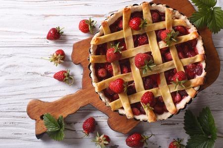 lahodný jahodový koláč v zapékací misky na stole. Vertikální pohled shora, rustikální styl