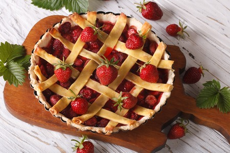 homemade strawberry tart and fresh berries in a baking dish on the table. horizontal view from above, rustic photo