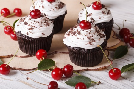 cupcakes: Beautiful chocolate cupcakes with white cream and cherry Black Forest close up on the table. horizontal Stock Photo