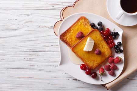 French toast with honey and berries on a plate