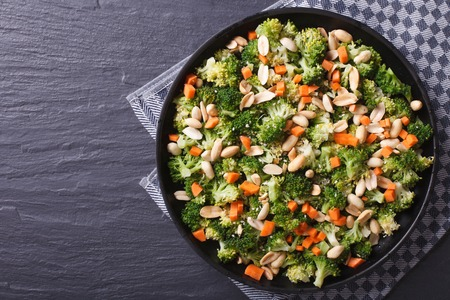 ensalada verde: Ensalada de br�coli con man� y zanahorias de cerca en un plato negro