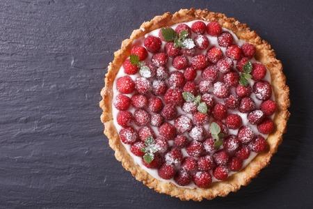 경치: 테이블에 신선한 나무 딸기와 민트 타트. 위의 가로보기