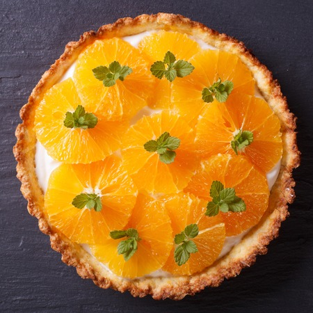 orange tart: Delicious orange tart with white cream and mint on a dark table close-up. view from above