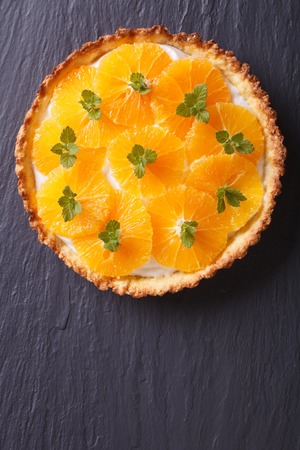 orange tart: Delicious orange tart with white cream and mint on a dark table. vertical top view Stock Photo