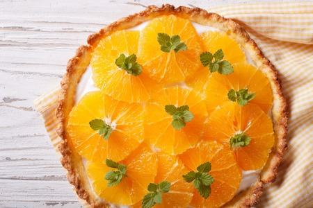 orange tart: Tasty orange citrus tart with white cream and mint close-up on the table. horizontal view from above Stock Photo