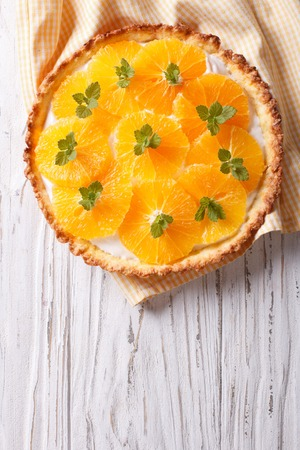 orange tart: Orange tart with cream and mint on the table. vertical top view
