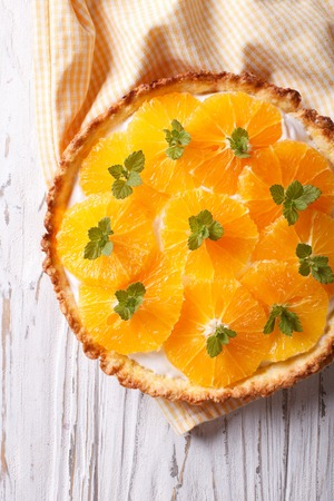 orange tart: Orange tart with white cream and mint close-up on the table. vertical top view