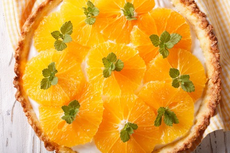 orange tart: Orange tart with a delicious cream and mint macro on the table. horizontal view from above Stock Photo