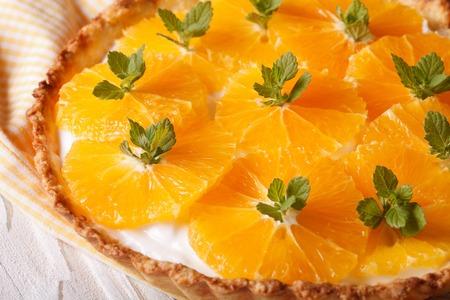 orange tart: Orange tart with cream cheese and mint macro on the table