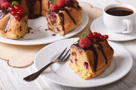 Piece gâteau au chocolat avec des baies close-up sur une plaque et le café Banque d'images