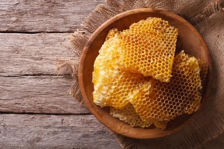 Goldene Honigwabe auf einem hölzernen Teller auf dem Tisch. horizontale Ansicht von oben