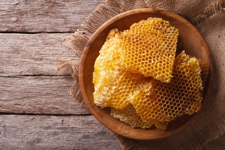 Golden honeycomb on a wooden plate on the table. horizontal view from above Stockfoto