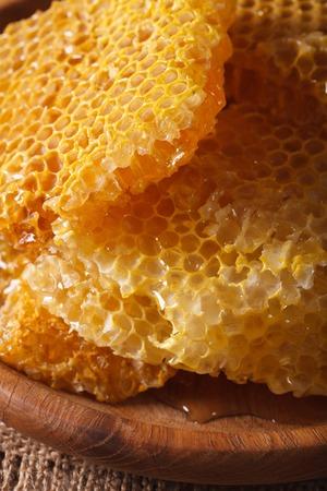 honey comb: Fresh golden honey comb on wooden plate macro