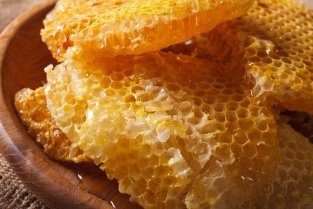 honey comb: Fresh golden honey comb on wooden plate macro. horizontal