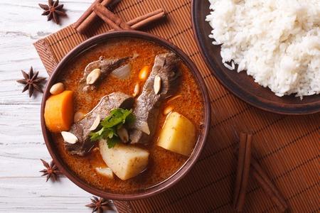 Hot tradizionale massaman manzo al curry tailandese con arachidi e riso lato piatto da vicino. vista orizzontale dall'alto