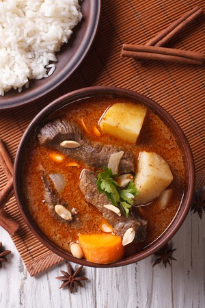 side of beef: Hot traditional Thai beef massaman curry with peanuts and rice side dish close up. vertical top view