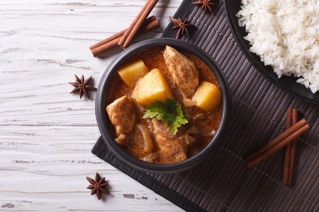 Thai massaman curry with chicken in a bowl and rice on the table. horizontal top view