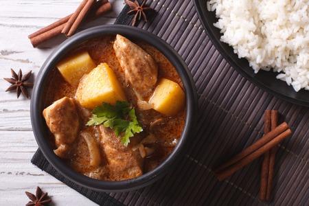arroz: Curry Massaman tailandés con pollo en un tazón y el arroz en la mesa de cerca. vista superior horizontal Foto de archivo