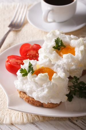 aristocrático: Breakfast aristocratic: sandwiches with baked eggs Orsini and tomato on a plate close-up. vertical