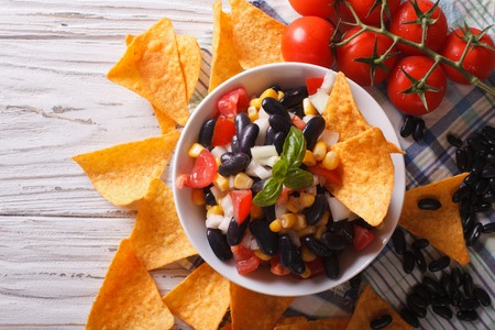 tortilla chips: Mexican salsa with beans in a bowl and corn chips nachos on the table close-up. horizontal view from above