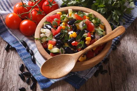 black beans: Mexican vegetable salad with black beans in a wooden bowl, close-up and ingredients on the table. horizontal