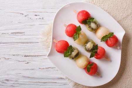 brochetas de frutas: Pinchos de la fruta con las bolas de sandía, kiwi y melón en una placa. Vista superior horizontal
