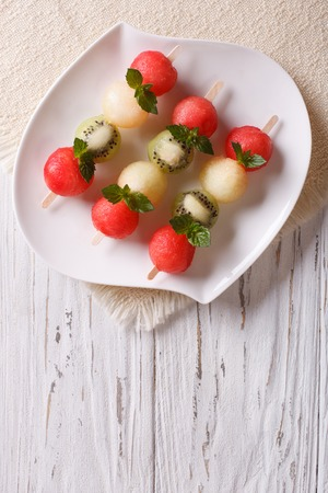 brochetas de frutas: Pinchos de la fruta con las bolas de sandía, kiwi y melón en una placa. vista superior verticales Foto de archivo