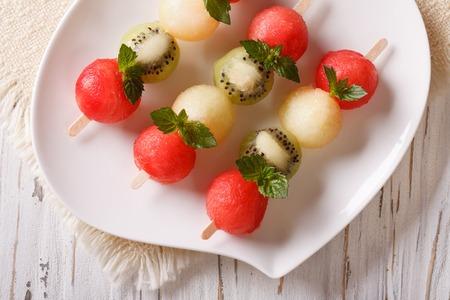 brochetas de frutas: Pinchos de la fruta con las bolas de sand�a, kiwi y mel�n en primer plano en un plato. vista superior horizontal