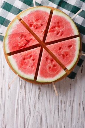 sliced watermelon: Pieces of ripe watermelon on a stick on the table. vertical top view