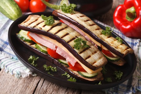 unusual vegetables: Unusual aubergine sandwich with vegetables, ham and cheese close-up on a plate. horizontal Stock Photo
