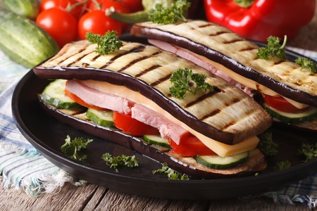 unusual vegetables: Unusual eggplant sandwich with vegetables, ham and cheese close-up on a plate. Stock Photo