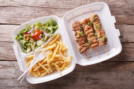 plates of food: Fast food: kebabs, fries and fresh salad in the tray on the table. horizontal view from above