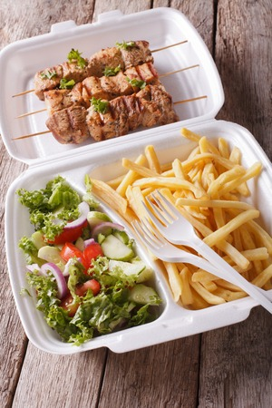 lunch tray: Lunch Box: kebabs, fries and fresh salad in tray close-up on the table. vertical