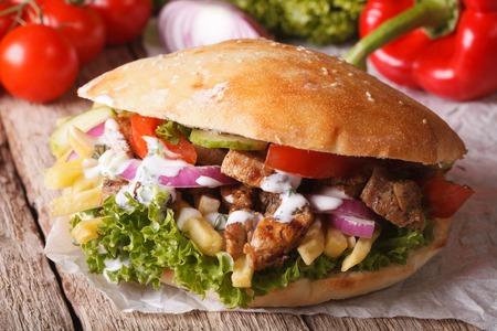 食欲をそそるサンドイッチ: テーブルの上の肉、野菜、フライド ポテトのクローズ アップとドネルケバブ。水平方向
