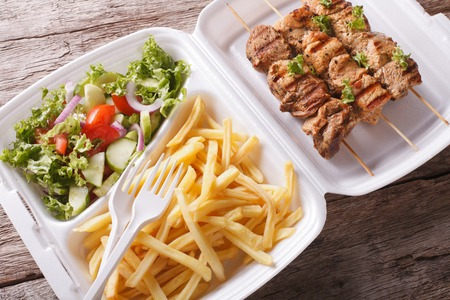 lunch tray: Lunch Box: kebabs, fries and fresh salad in tray close-up on the table. Horizontal