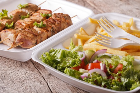 doner: Fast food: kebabs, fries and fresh salad in tray close-up on the table. horizontal Stock Photo