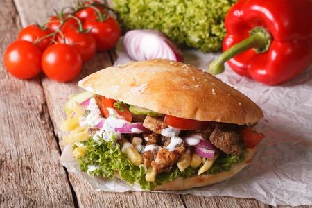 Fast Food: döner kebab hús, zöldség és sült burgonyával közelről az asztalra. vízszintes