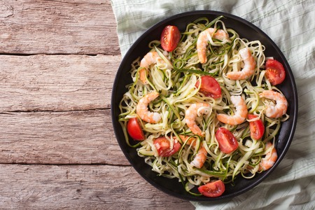 shrimp: zucchini pasta with shrimp and tomato on a plate. horizontal top view