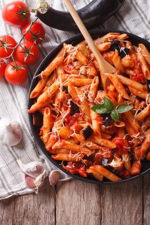berenjena: Comida italiana: Pasta alla Norma de primer plano en la mesa y los ingredientes. vista superior verticales Foto de archivo
