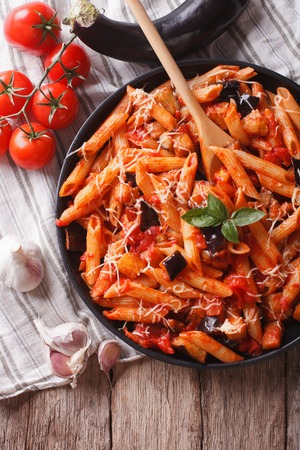 Italian food: Pasta alla Norma close-up on the table and ingredients. vertical top view