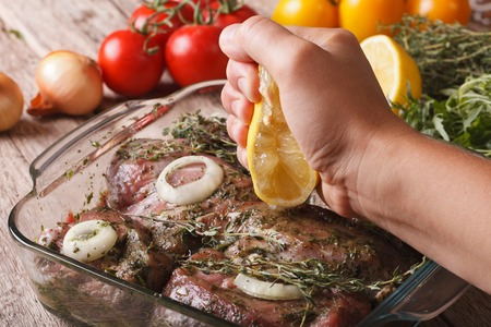 クッキング: マリネ肉のクローズ アップにレモン汁を絞る。水平方向 写真素材