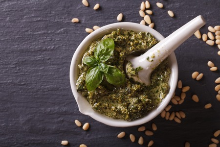 nuts: Italian pesto sauce in a mortar close-up on the table. horizontal view from above
