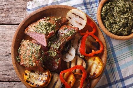carnes y verduras: Carnes jugosas y verduras a la parrilla con salsa de pesto en primer plano en un plato. vista superior horizontal Foto de archivo